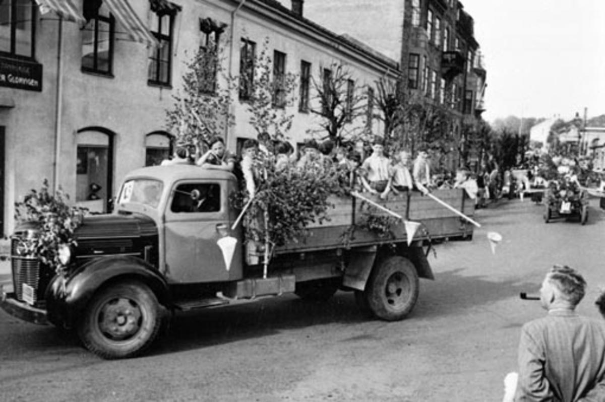 """HAMAR RØDE KORS. BARNEHAGEFONDET. BARNAS DAG 3. JUNI 1951. INNSAMLING TIL INNTEKT FOR NY BARNEHAGE. STOR BARNEKORTESJE. START HJØRNET PARKGT. /ST. OLAVSGT. KL. 16. RUTE PARKGT. STRANDGT. SKOLETORVET, TORVGT. ØSTRE TORG, VANGSVEGEN, ST. OLAVSGT OG TILBAKE TIL UTGANGSPUNKTET. BARN PÅ LASTEBILER UTKLEDD I KOSTYMER- MED HOV FOR INNSAMLING AV PENGER. GUTTESPEIDERE PÅ LASTEPLANET. VOLVO """"RUNDNOS"""" 1946-54 LASTEBIL"""
