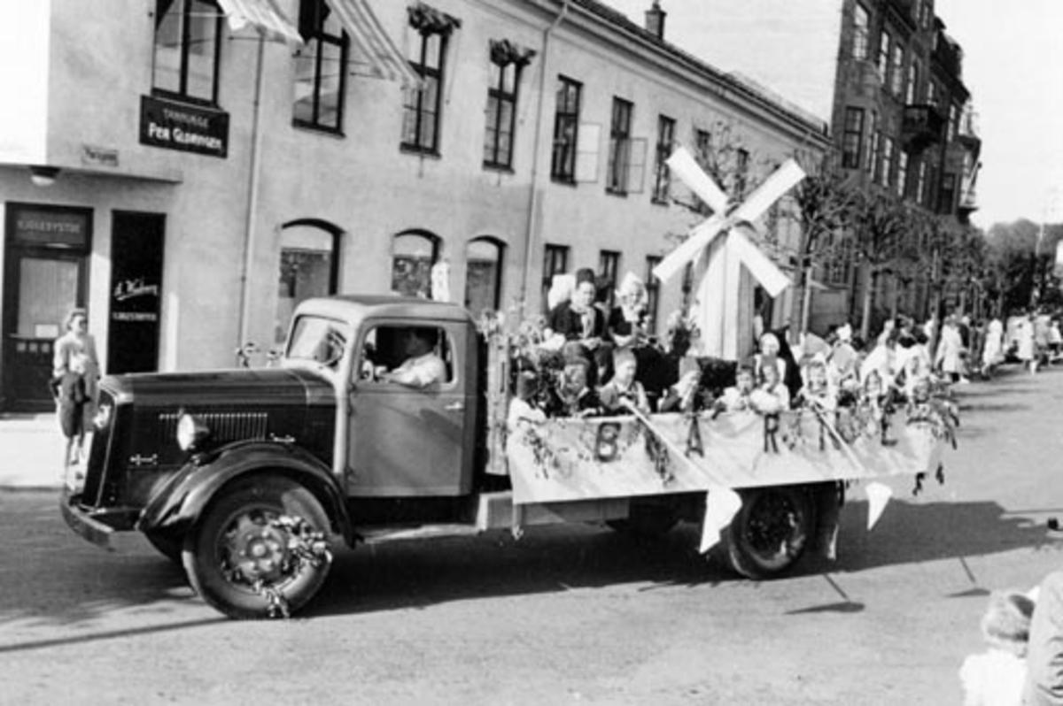HAMAR RØDE KORS. BARNEHAGEFONDET. BARNAS DAG 3. JUNI 1951. INNSAMLING TIL INNTEKT FOR NY BARNEHAGE. STOR BARNEKORTESJE. START HJØRNET PARKGT. /ST. OLAVSGT. KL. 16. RUTE PARKGT. STRANDGT. SKOLETORVET, TORVGT. ØSTRE TORG, VANGSVEGEN, ST. OLAVSGT OG TILBAKE TIL UTGANGSPUNKTET. BARN PÅ LASTEBILER UTKLEDD I KOSTYMER- MED HOV FOR INNSAMLING AV PENGER. VOLVO 1935-40 LASTEBIL