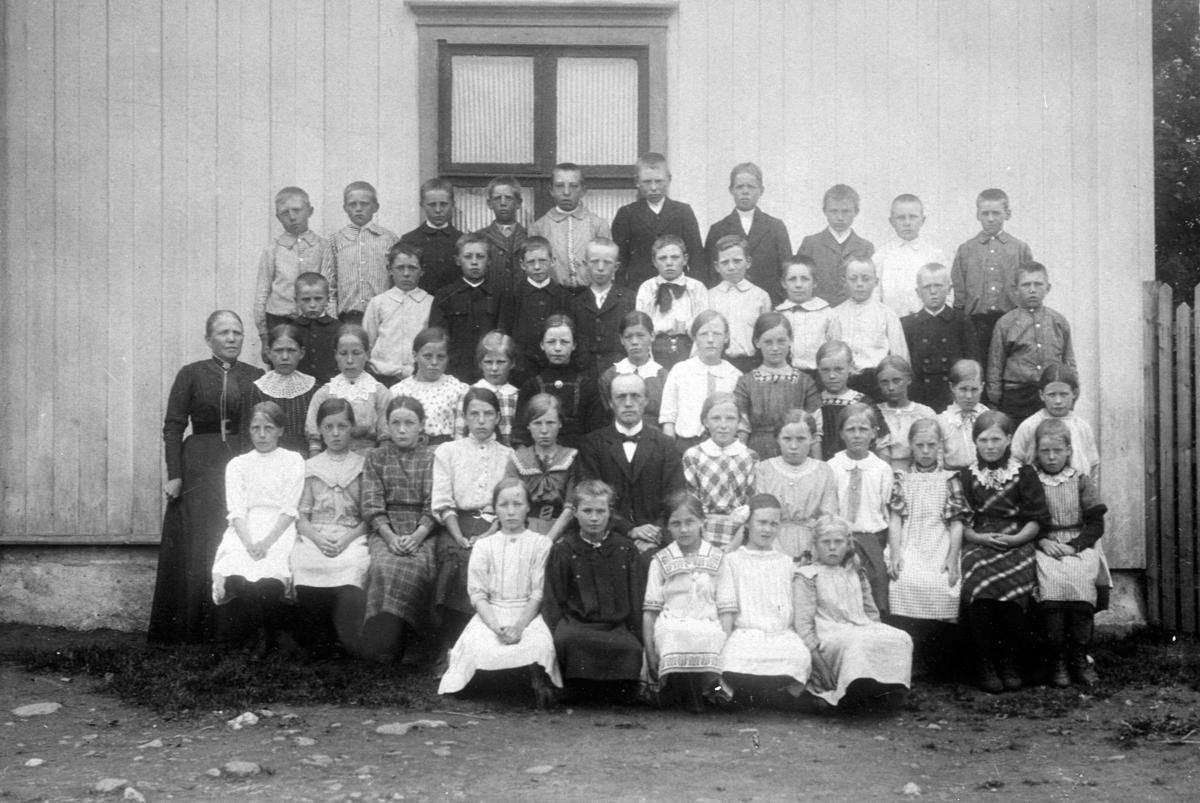 Stor gruppe skoleelever oppstillt utenfor Kirkekretsen skole, Veldre, Ringsaker. Lærere er Oline Rud og Johan Aarskog.