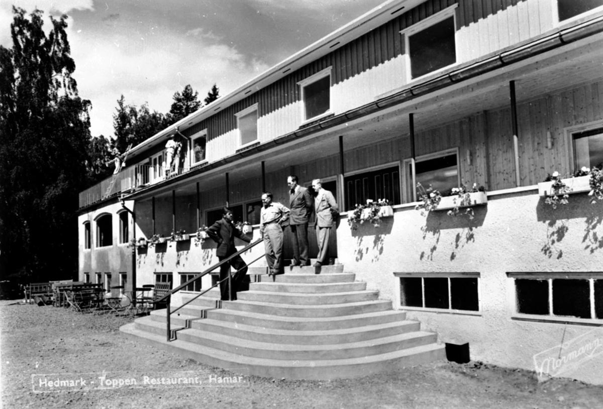 Inngangspartiet til Hedmarktoppen restaurant, Hamar. Fire menn i trappa. Malere i stige.