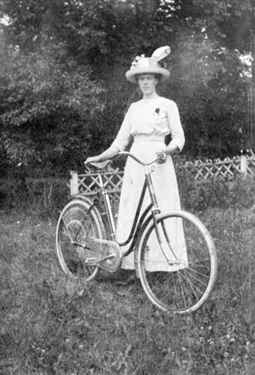 Thea Amundsdatter Berger (1889-1965) med sykkel. Kjole og hatt. Hun ble gift med Halvor Hovie.