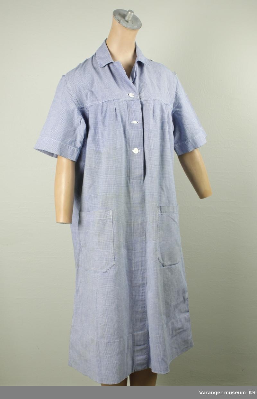 """Norske Sanitetskvinners """"søsteruniform"""" i blått og hvit. Uniformen er i skjørtelengde. Kortermet med enkel krage. Har to store påsydde lommer i front. Knapper i øvre halvdel. Registreringen består av to identiske uniformer, den ene lappet under armene."""