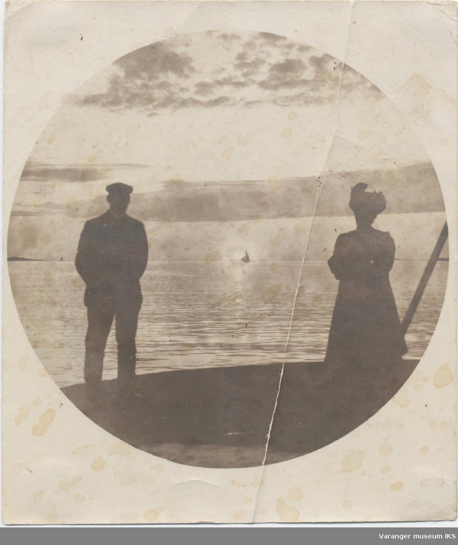 Siste midnattsol 27. juli 1900, mann og kvinne ytterst på østre moloarm i forgrunnen