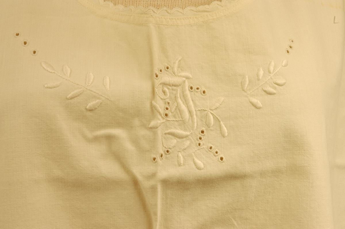 Underkjole i ubleka bomullslerret med initialer i engelsk broderi ved halsringinga på forstykke. Rund halsåpning med tungekant. Skulderstroppene lukkes med en knapp på hver skulder. Både for- og bakstykket er laget av ett stoffstykke. Maskinsydd.