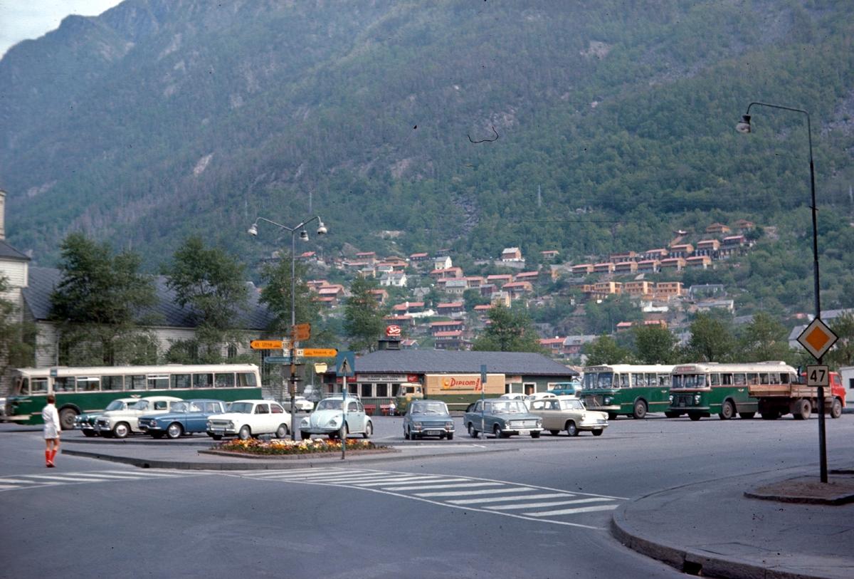 Vegkryss, vegskilt, parkeringsplass, bilar, bussar, pakkesentral, Odda kyrkje, blomebedd, byggefelt på Freim, fotgjengarovergang