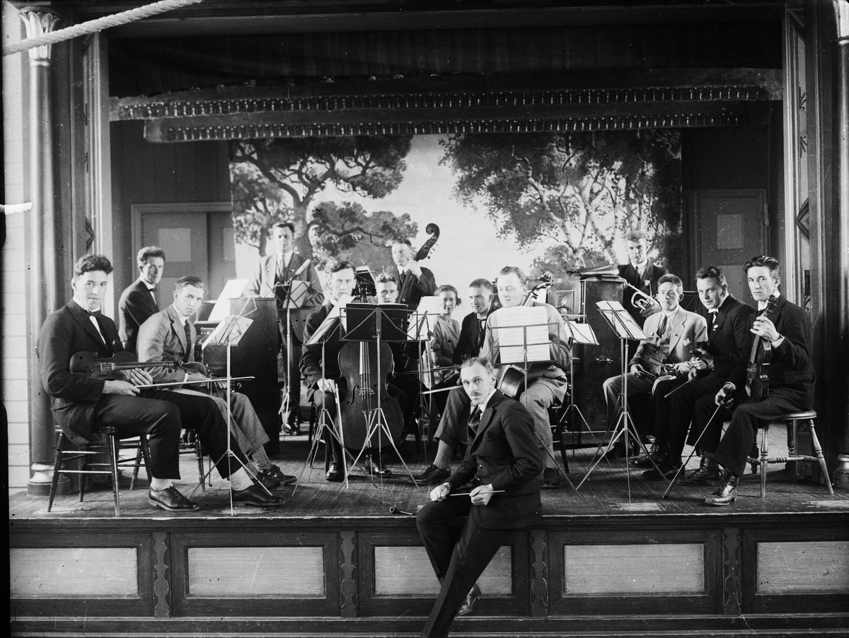 Ivar Skårset sittende på scenekanten med orkester i bakgrunnen