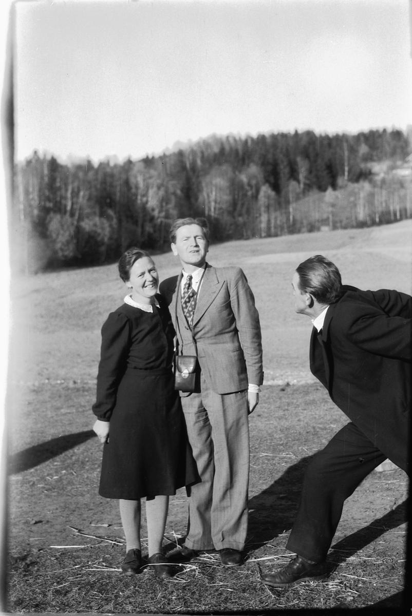 To menn og ei kvinner foran et jorde.