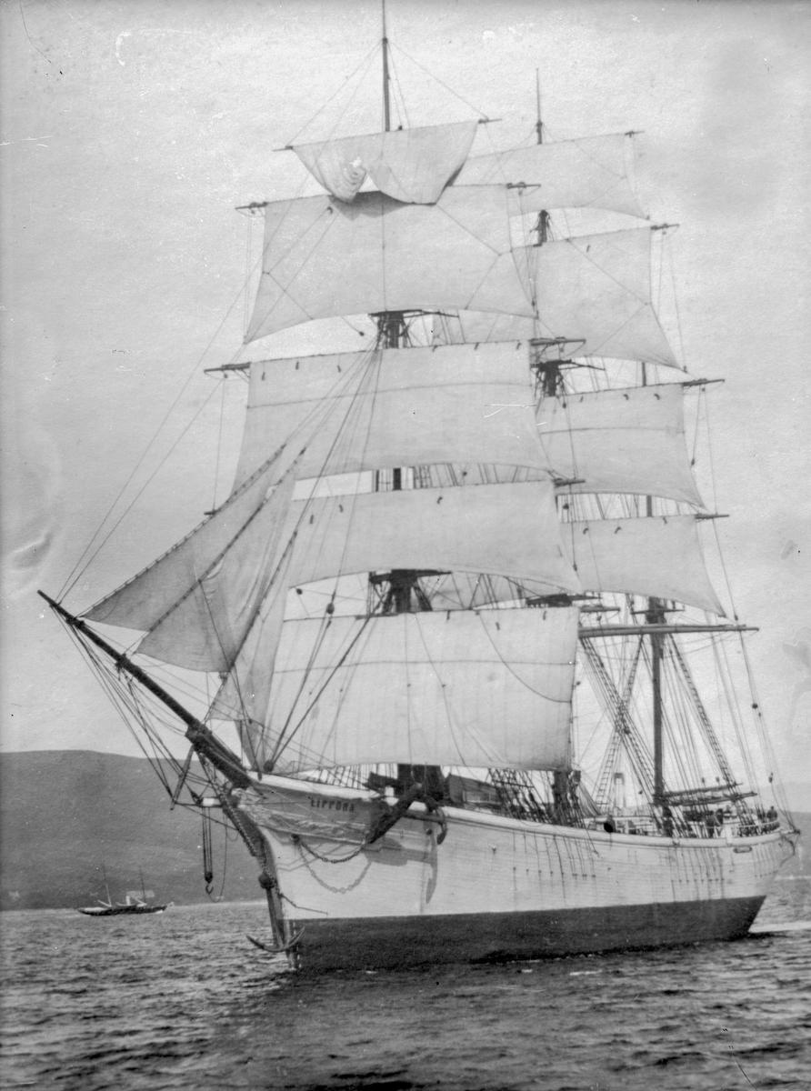 """Fullriggeren """"Zippora"""" for fulle seil langs kysten, med liten båt og høye fjell i bakgrunnen."""