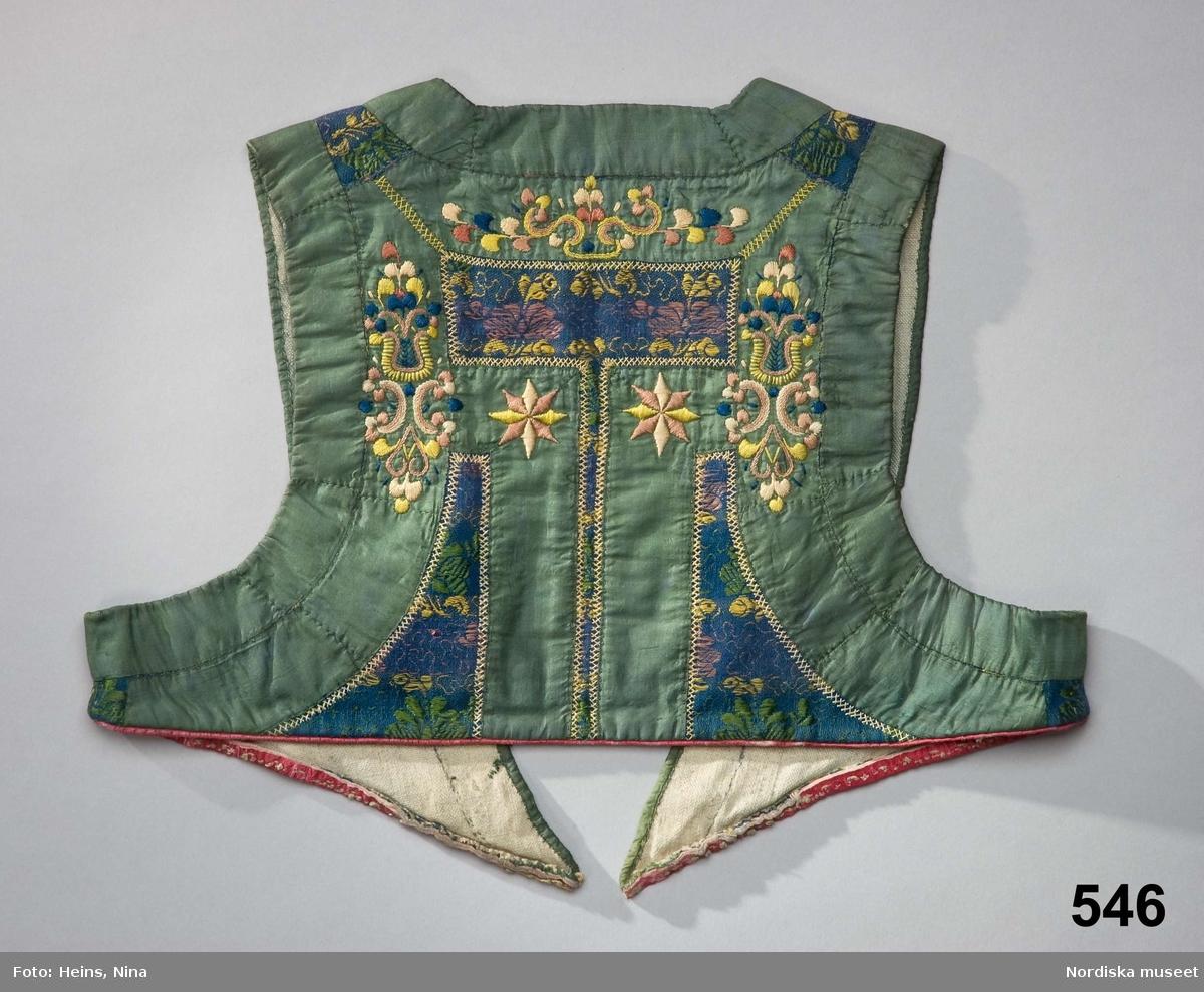 Liv som suttit ihop med skinnkjol, sk. klocka eller päls eftersom den hade fårskinnspälsen inåt. Av halvsiden, blå botten i bomull/silke med invävda blomsterornament och slingor i silke i rosa, gult och grönt. Livet mycket kort och till stor del täckt med påsydda 2,5-3,5 cm breda gröna sidenband som i ryggen lämnar en ruta av tyget öppen. Kring alla bandkanter i ryggen dekorsömmar i flätsöm med gulrosa silke: Broderi i plattsöm även på banden i ryggen i rosa, tegelrött, gult och mörkblått silke. Foder av oblekt linnelärft. Broderiet sytt tvärs igenom fodret. Nederkanten har passepoal av rött saffianskinn. Märken efter den bortsprättade kjolen. /Berit Eldvik 2008-04-07