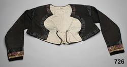 Kvinnotröja, troligen  brudtröja, av svart redgarnsylle. Kort modell med långt ryggskört. 2 framstycken/sidstycken med infällda skörtkilar i sidorna och cirkelrunt urtag fram över bröstet. Ett ryggstycke som har rätvikliga sömmar mot sidorna, avslutade i 2 skörtveck. Över ryggsömmarna sytt i flätsöm med svart silke och vid skörtvecken klarblå prickar sydda i plattsöm Isydd svängd  ärm med en söm,10 cm långt ärmsprund  med en hake och hyska, axelkarmar klädda med svarta sidenband..  Runt framstycken och hals bård av 3 cm brett svart sidenband.  Ärmarna kantade nederst med brunt sammetsband sen ett mönstervävt sidenband med blommor och streck i gult, grönt, vitt och ljusblått  samt guldtråd på lila botten, och överst svart sidenband. Knäppt med en hake och hyska på var sida om urringningen. Foder av blekt halvlinnelärft. Har enligt Bruzelius tillhört en torparhustru ( husmanshustru), är troligen något äldre än t.ex. tröjan 545. Tröjan är av den typ som N.G.Bruzelius har beskrivit för brudar i Herrestads hd under förra delen av 1800-talet. Se även S. Svensson: Skånes folkdräkter, Sthlm 1935. /Berit Eldvik 2010-11-25