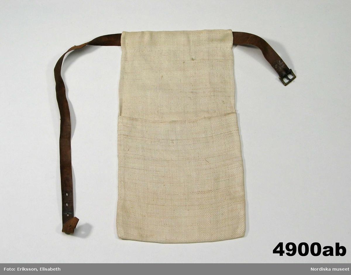 """a-b. Kjolväska med bälte. rem längd 80 cm, bredd 2,1 cm                                      väska längd 38 cm, bredd 21 cm enkel kjolväska av ett avlångt stycke liksidig linnekypert, vikt till en ficka och med dragsko upptill med ett iträtt brunt läderbälte med remsölja av mässing. Hör till hel vallflickedräkt inv.nr 4900 - 4908 Huvudliggaren: """"Slekespåse. Skall fyllas med mjöl och salt åt jäntan att gifva kreaturen. Skinnremmen sätts fast omkring midjan, utanpå förklädet, samt hvita påsen vid högra sidan.""""  /Berit Eldvik maj 2006"""
