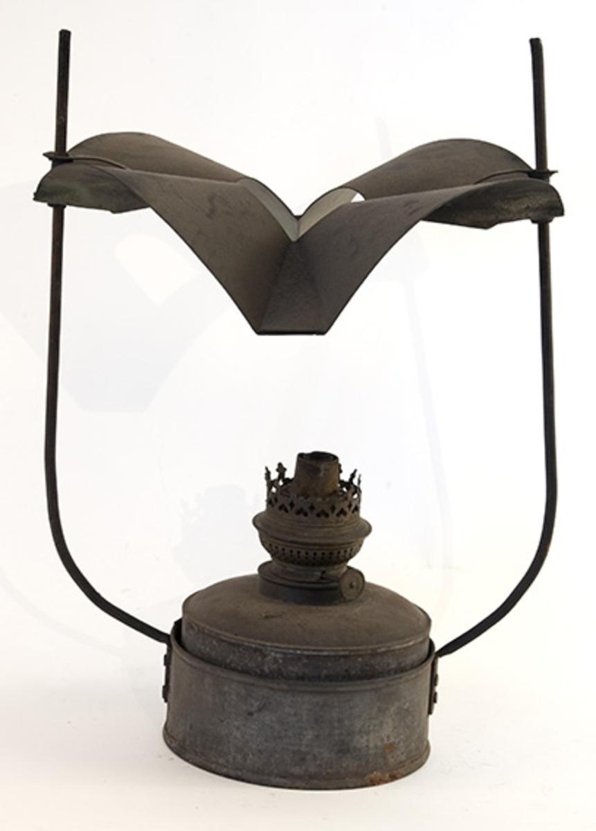 Parafin bordlampe. Sirkelformet brenner/parafinbeholder. Metallskjerm festet til to opprettstående metallstenger.