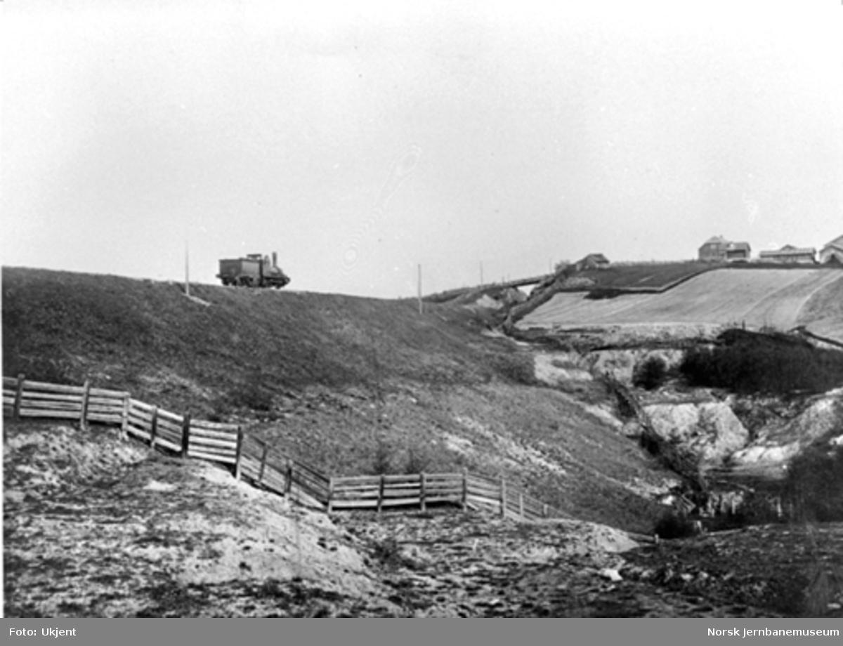 """Damplokomotiv på """"Haugenstuen Bank""""; den svære fyllingen som i 1861 erstattet en trebru"""