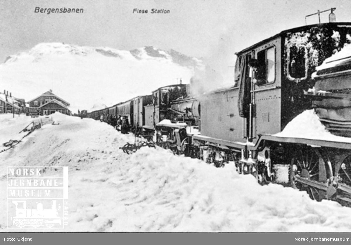 Vinterbilde fra Finse stasjon med østgående persontog trukket av to damplokomotiver av type 18 i spor 1