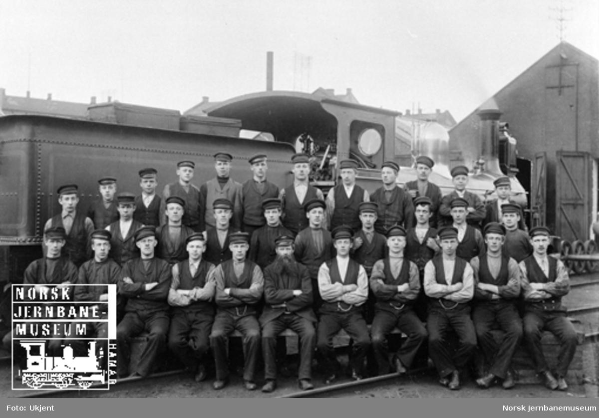 Gruppebilde av lokomotivpussere ved Hovedbanen fremfor et damplokomotiv av litra C