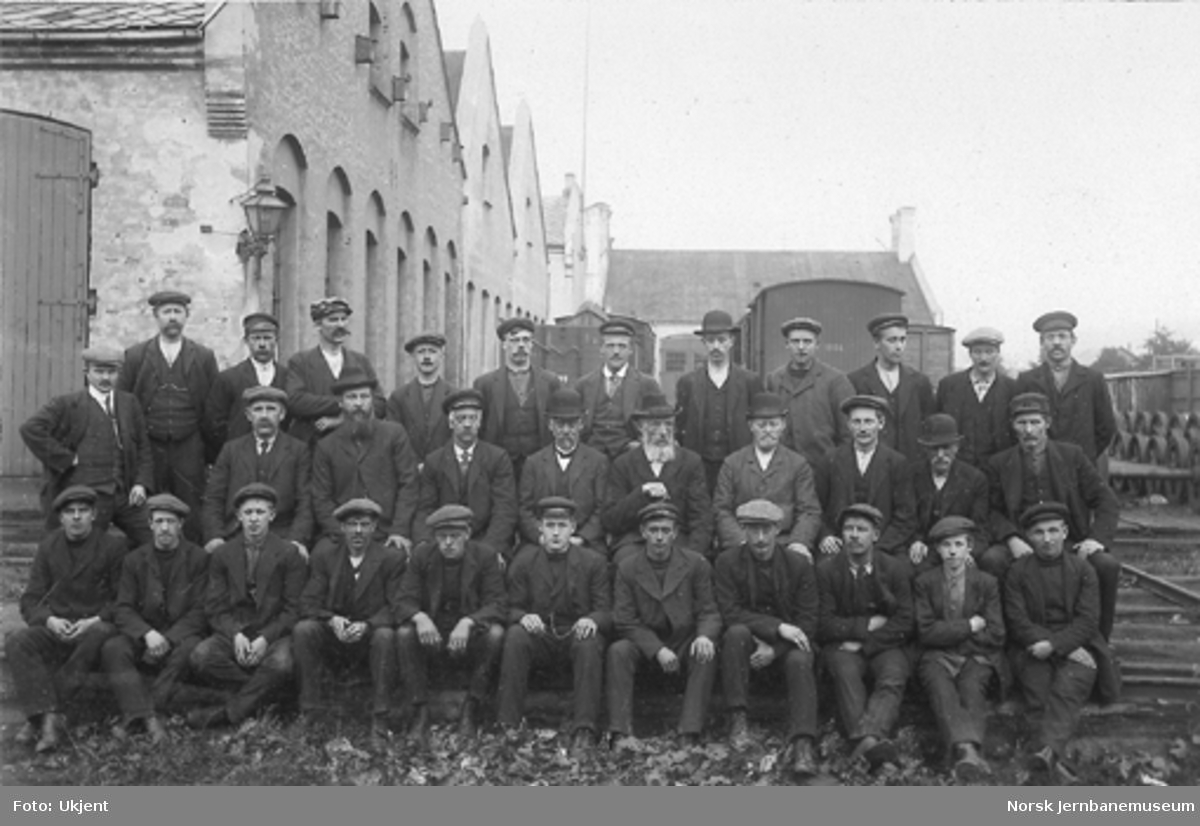 Gruppebilde av personalet i snekker- og vognverkstedet på Brattøra i Trondheim. I bakgrunnen til venstre malerverkstedet, videre hjørnet av forrådsbygningen med flaggstangen og helt i bakgrunnen kjelverkstedet