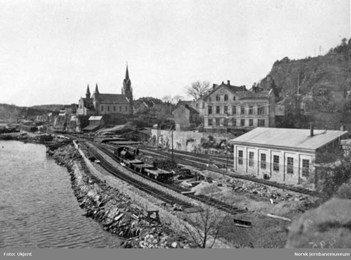 Kragerø stasjon, oversiktsbilde med lokstallen i forgrunnen, et damplokomotiv med arbeidstog og stasjonen i bakgrunnen
