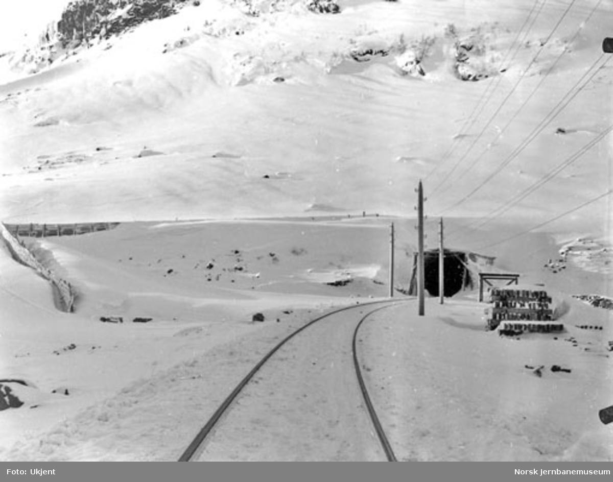 Linjeparti langs Bergensbanen vinterstid med snøskjermer og en overbygget tunnelinngang