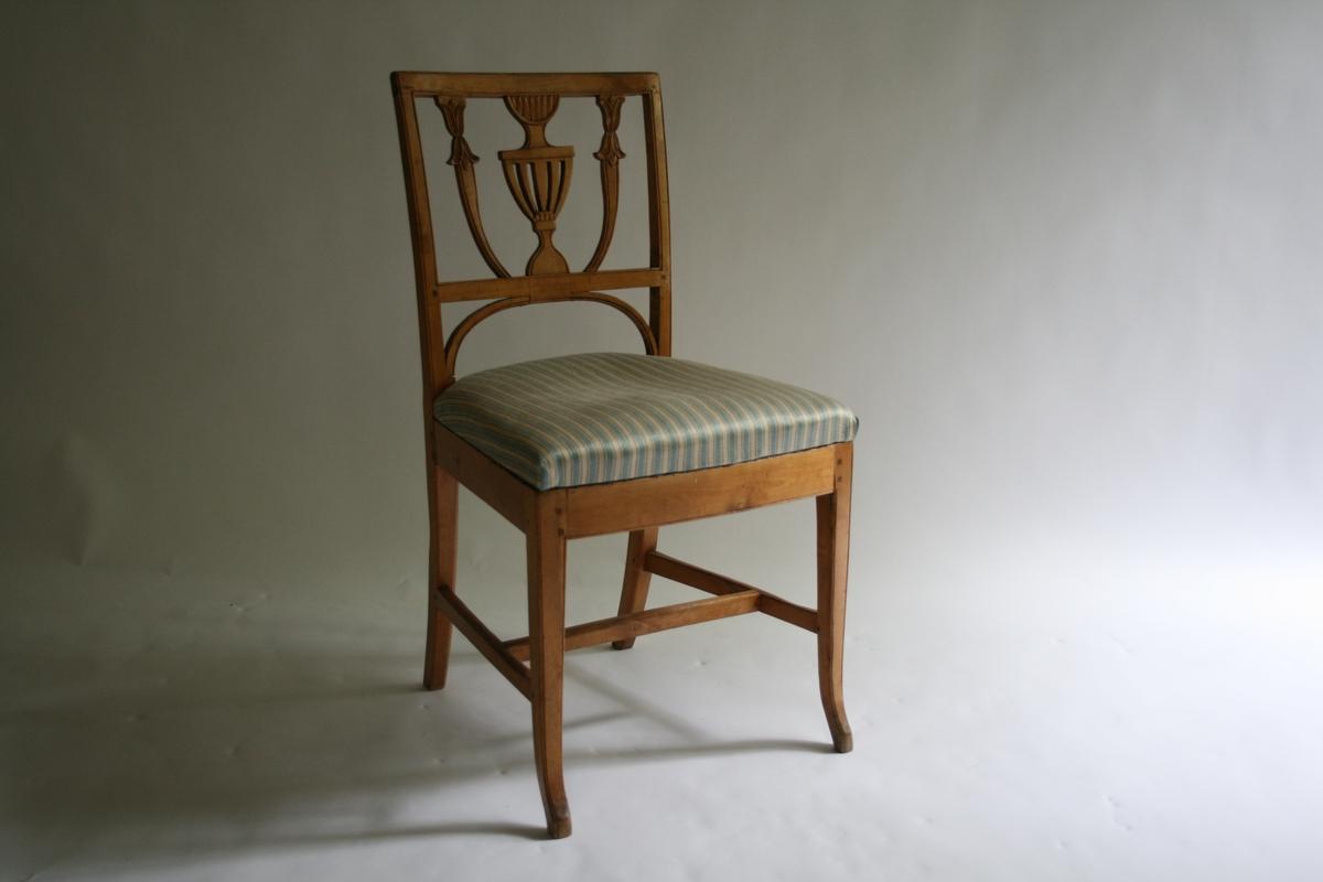 Motiv stolrygg: en urne.  Trekket, lys blått og lys grått like striper med en mørkere grå tråd innimellom, håndvevet. En av 9 bjerketres stoler m/stripet trekk.