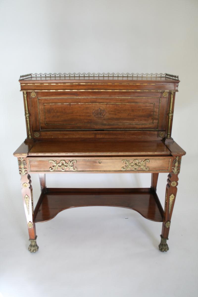 """Skrivebord eller sekretær i mahogni. Skuff med skriveklaff som kan trekkes ut. Klaff som kan skyves opp, med små skuffer og rom bak.  Beslag og ornamenter i messing eller brennforgylt bronse.  Antagelig svensk, seinempir (""""Karl Johan-stil)"""