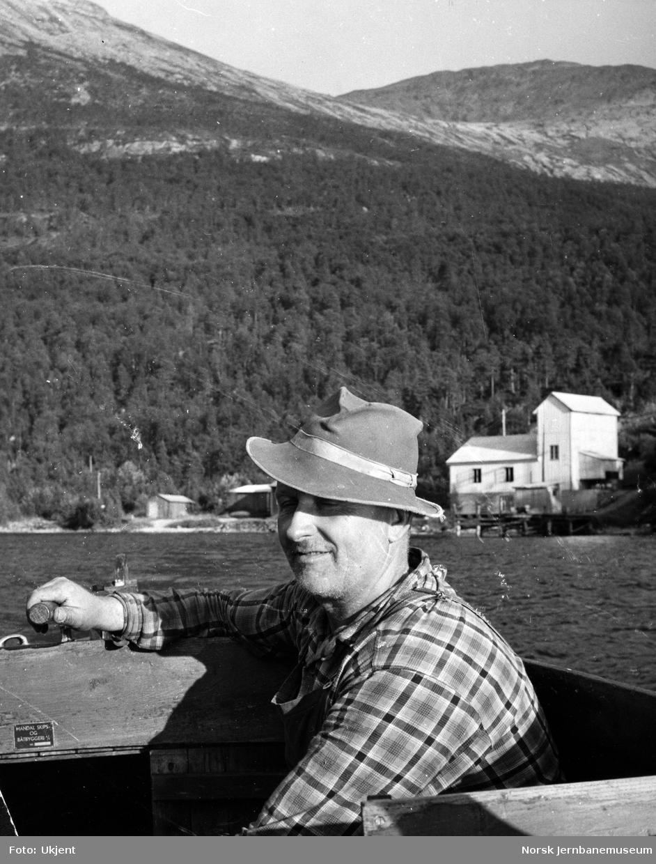 Maskinist Arne Fredriksen på Nordlandsbaneanleggets med Røyrvatn kraftstasjon i bakgrunnen