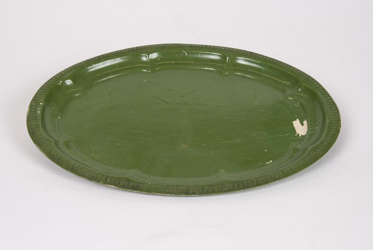 Oval bricka av plåt. Ommålad i grön färg.