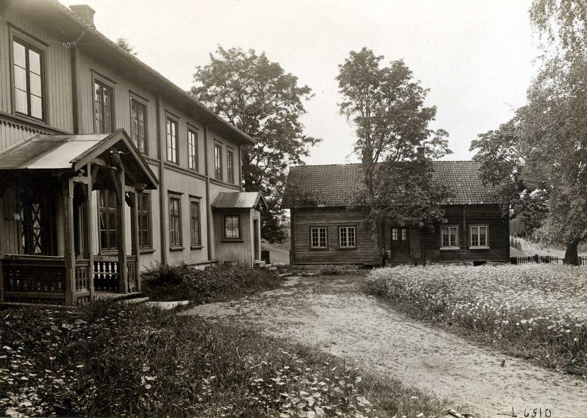 Plogstad, Ullensaker, Øvre Romerike, Akershus. Våningshuset og et mindre hus mot gårdsplassen og blomstereng.