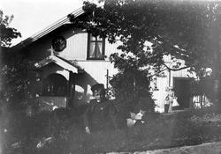 Portrett av 2 gutter med lue liggende i gresset foran bolighus i sveitserstil. Guttene er sønner av klokker Busland i Hurum. der fotografens svoger var prest. Kvinne med to barn i bakgrunnen.  Fra malerinne Juliane Fredrikke Langbergs (1856-1930) samling, tatt ca.1895-1910 med motivkrets slekt og venner samt steder tilknyttet samvær med disse.