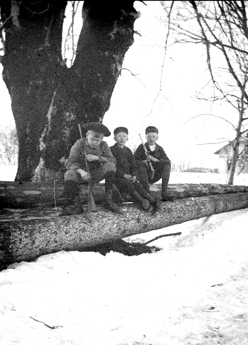 Portrett av 3 gutter med lue sittende på tømmerstokker med geværer i hendene.  T.v. Olaf L. Holm, sønn av sokneprest i Hurum, Olaf A. Holm, fotografens svoger. De to andre guttene er sønner av klokker Busland i Hurum. Muligens  på Hurum prestegård. Fra malerinne Juliane Fredrikke Langbergs (1856-1930) samling, tatt ca.1895-1910 med motivkrets slekt og venner samt steder tilknyttet samvær med disse.