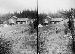 Mann med hatt (Gulbrand) står ved gjerde foran huset på Holo