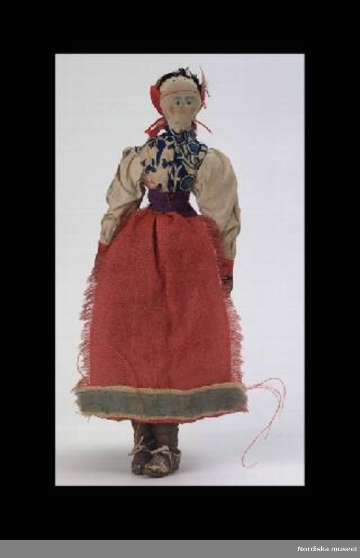 Inventering Sesam 1996-1999: H 23 cm Docka, hemtillverkad med stoppad tygkropp, målade anletsdrag, brunt hår av garn, klädd i malungsdräkt:  vit blus av linne, blå linnekjol, rött ylleförkläde med siden bård, mönstrad linneschal och rött hårband av ylle, bruna läderskor. Enligt äldre katalogkort tillverkad ca 1860 av malungskulla i Bräckgården, Floda socken, Dalarna.