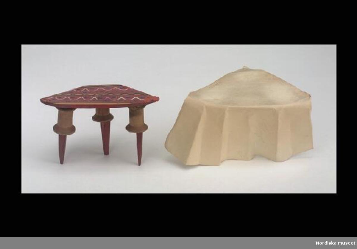 Inventering Sesam 1996-1999: a) Bord L 13 cm, B 6,7 cm, H 8,5 cm b) Duk L 19 cm, B 16 cm Bord med duk till dockskåp. a) Bord av trä, trekantigt med avfasade hörn. Skivan målad i rött med mönster i flera färger. Tre ben med överdel av syrullar och fyrkantiga avsmalnande underdel. Benen fastsatta med rött lack. Bordet har ursprungligen haft ett annat utförande. b) Duk av vitt papper, trekantig, den hängande delen veckad. Tillhör dockskåp inv nr 229.151 (inventarier 229.152-229.353).  Skåpet ordnat av fru Emilie Kihlberg, f Svensson (1836-1904), gift 1856, för hennes 3 styvbarn och 10 egna barn. Se dockskåpets kat.kort för mer info. Leif Wallin dec 1997