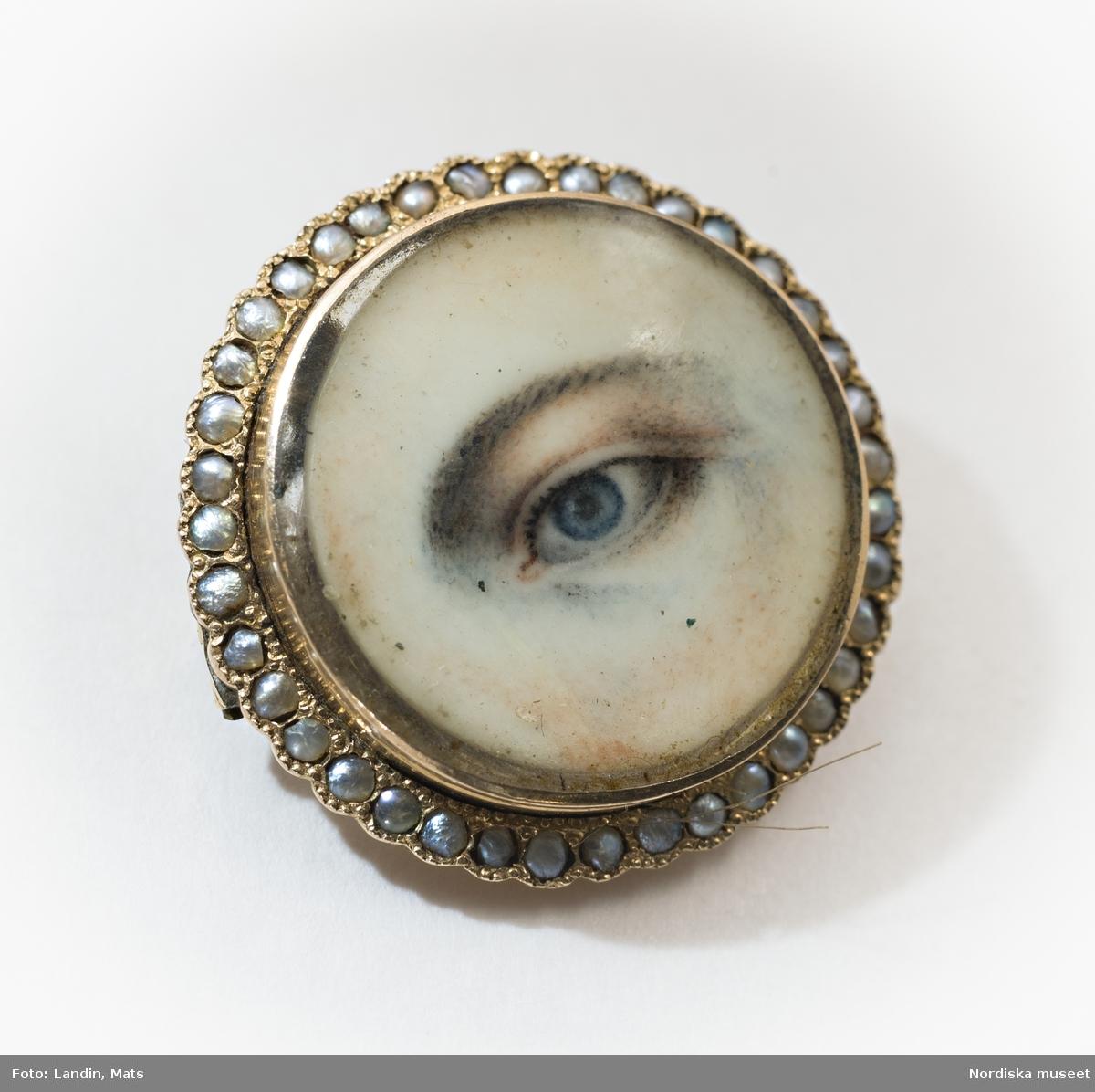 Hårlock under tunn benplatta med målat öga.