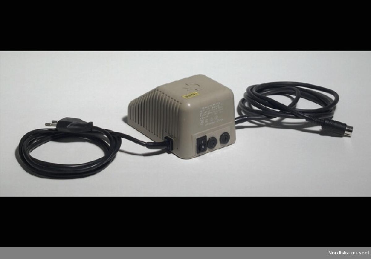 """Inventering Sesam 1996-1999: L 13,5 cm B 8,5 cm H 7 cm Transformator med grått plasthöljje. Randig på sidorna, Commodores logotype ovanpå; ett C med två streck (C=, ungefär). Baktill svart avstängningsknapp och text """"TRANSFORMATOR / PASRT - NO 902503-11"""" mm. F¿r 5 volt - 1,5 ampère. Två fasta svarta sladdar, en med stickkontakt och en med DIN-kontakt. Ovantill gul pappersetikett """"369"""". Undertill stämplad i gult """"20 (eller 26) APRIL 1985"""". Axel Brundin (född 1977) fick datorn i julklapp. Den var köpt från pojkarna Norman (födda 1971) som tidigare använt den. Dataspel och tillhörande föremål; Tangentbord ivn.nr 321.617 kasettbandspelare inv.nr 321.618, transformator inv.nr 321.619, Kasettväska med kasettband med olika dataspel inv.nr 321.620:1-24, tre joy sticks inv.nr 321.621 och 321.622, skokartong inv.nr 321.623 (i vilken kasettband f¿rvarades)  och Kasettband med spel 321.624-321.639 Instruktionsböcker, band- och kundförteckning finns på arkivet. Bilaga EB 1995  [=Elisabeth Brundin] Leif Wallin 1998"""