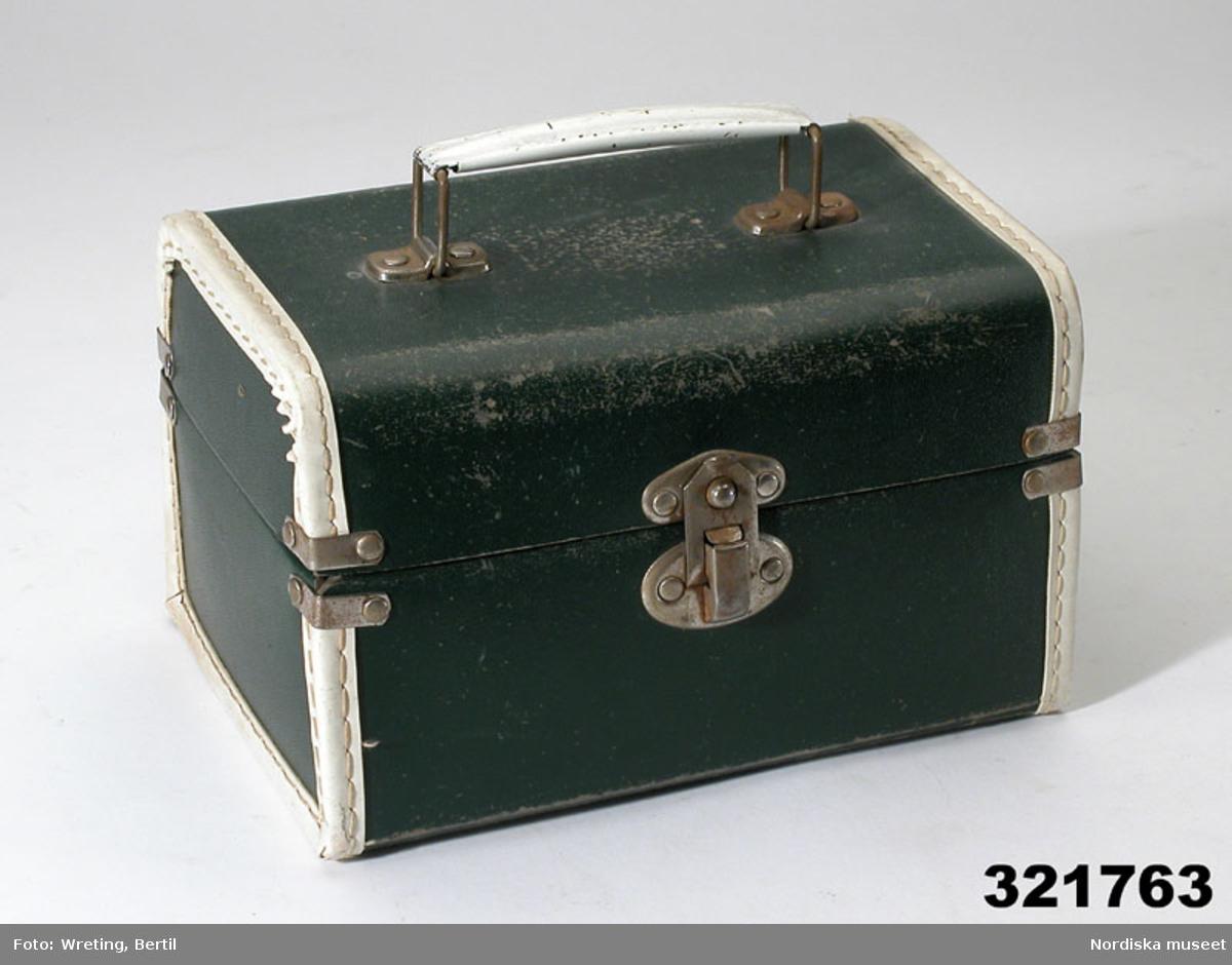 """Katalogkort: """"Beautybox f. lek. 1950-talet. Beauty-Box av pressad papp, grön utvändigt, brunmelerad invändigt. Underdel och lock sammansatt med nitar, rundade kanter på locket. Sidokanterna klädda med vit plastremsa. Lås av metall, på locket handtag av vitmålad plåt. Har använts av Inga Bergner, född 1951. Se Torsten Bergners personarkiv, acc.nr. 10/1996. Anna Lalic april 1996"""""""