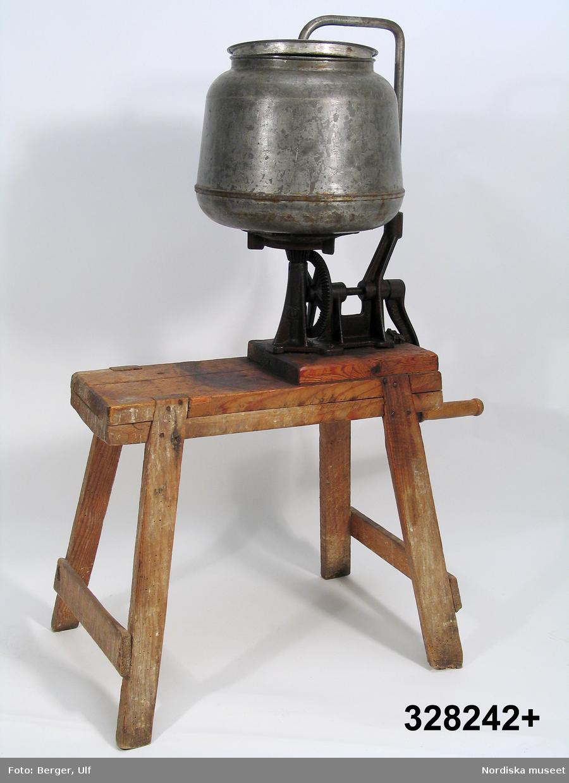"""Cylindrisk svagt konande smörkärna monterad på trästativ av furu. Kärnhuset är tillverkat av förzinkad järnplåt. Invändigt en ställbar vinge, anbringad på ett utvändigt fäst stativ. Med en vev, av gjutjärn med trähandtag, kopplad till en utväxling under själva kärnan bringades hela cylindern till snabb rotation.  Smörkärnan är tillverkad av AB Gefle Separator omkring 1910-1915. Modellen benämnes Ceres n:r 1. Kärnan användes av en småländsk torparfamilj under 1930-40 talen.  Nedan den beskrivning som givaren Axel Kronblad lämnade skriftligt tillsammans med kärnan: """"Denna smörkärna inköptes av mina föräldrar, (Ester och Ernst Kronblad) vid deras tillträde till torpet Hamburg, som löd under slottet Teleborg utanför Växjö. Slottet var under många år i familjen Bondes ägor. Kärnan inköptes begagnad, tillverkaren är okänd. Tillverkningsåret bör vara från åren 1870 - 1880. På veven framgår det av en text att arbetsmomentet skulle utföras med """"55 rev/minut""""! Från torpet Hamburg följde så kärnan min familj den 14/3 -37 till vårt nya hem - Södratorp i Värends Nöbbele. Där var den i tjänst till år 1950 då torpets mjölk började levereras till mejeriet i Växjö. Men under hela den tiden nämda tiden framställdes torpets smörproduktion med denna kärna. Som mest hade torpet fem kor, när mjölken """"rann till"""" som mest, kunde det förekomma att vi kärnade 3 - 4 gånger i veckan. Kärnan rymmer 6 - 7 liter grädde, den delprodukt som erhölls med den likaledes handvevade separatorn. Varje kärning gav 2 - 3 kg smör, detta saltades och vägdes upp i 1 kilos """"trillingar"""" med besman. (Den tidens våg.) Smöret såldes sedan till de hushåll i byn som ej hade egna djur. Priset för ett kilo smör, minns jag, låg fast under hela andra världskriget, nämligen 4,50 kr/kg. Under min skolgång så var det jag som stod för transporten av dessa förbeställda """"smörtrillingar"""". Och lyckan blev för mej total när någon av våra kunder gav mej en femma jämt, ty en 50-öring var en mycket välkommen inkomst för en 7 - 11 år"""