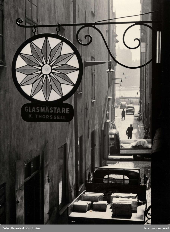 Skylt i smide och glas för glasmästare K. Thorssell i Gamla stan, Stockholm
