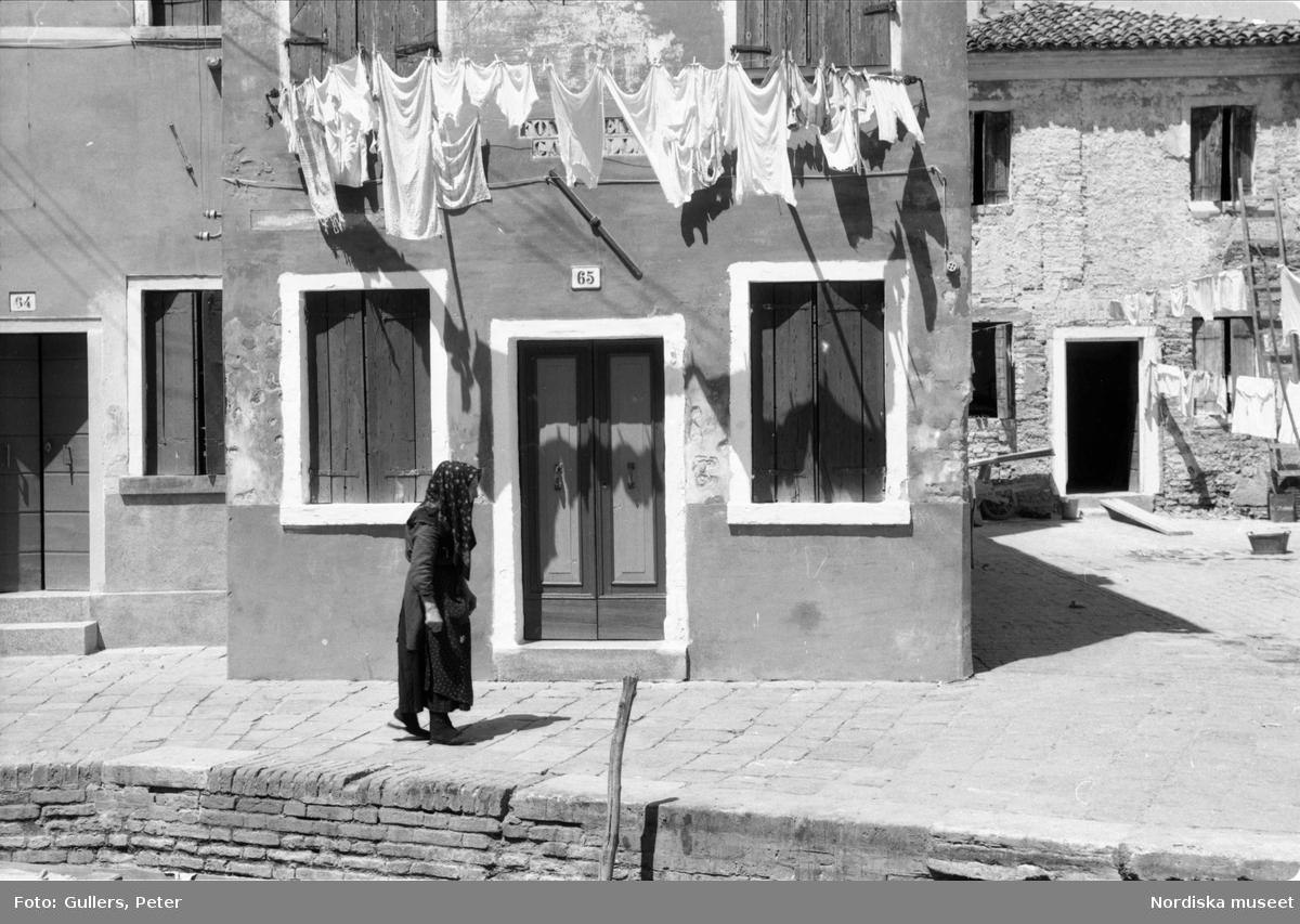 Äldre kvinna i mörka kläder och sjal över huvudet går förbi ett hus där vit tvätt hänger utanför fönstren. Skarpt solsken. Italien