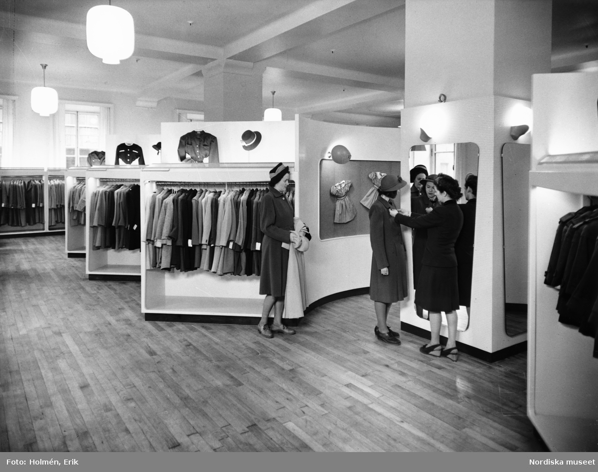 Interiör från Nordiska Kompaniet. En expedit hjälper en ung flicka att prova en kappa. Bakom står en kvinna och håller i en ljus kappa. I bakgrunden hänger kappor, hattar och barnkläder.