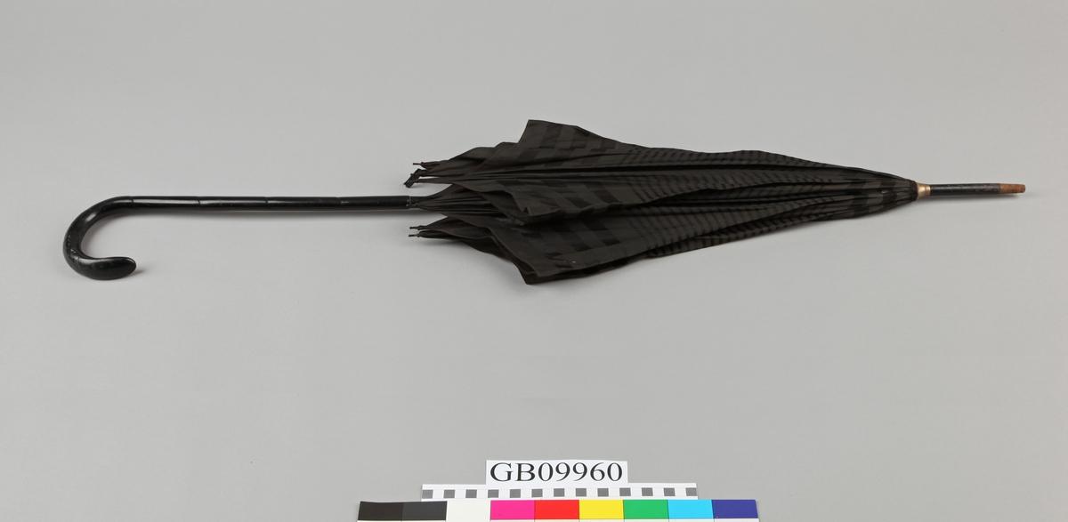 Langt glatt treskaft med buet håndtak. Stripet silke. Metallspiler.