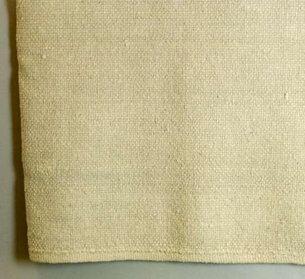 Filt av beige ull i panama. Påsydd kant i samma färg och material i kypertteknik.