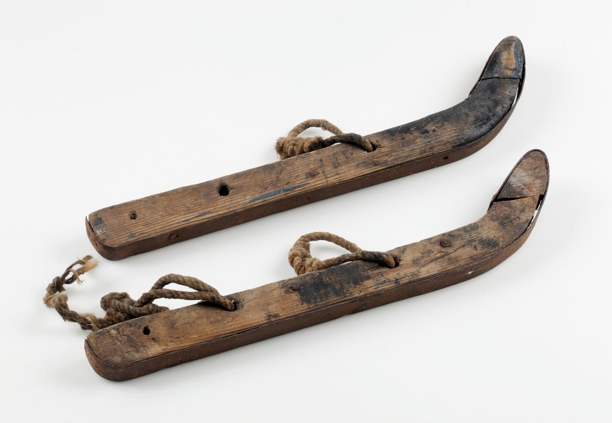 Ett par skridskor av trä, järnskodda. Snören.