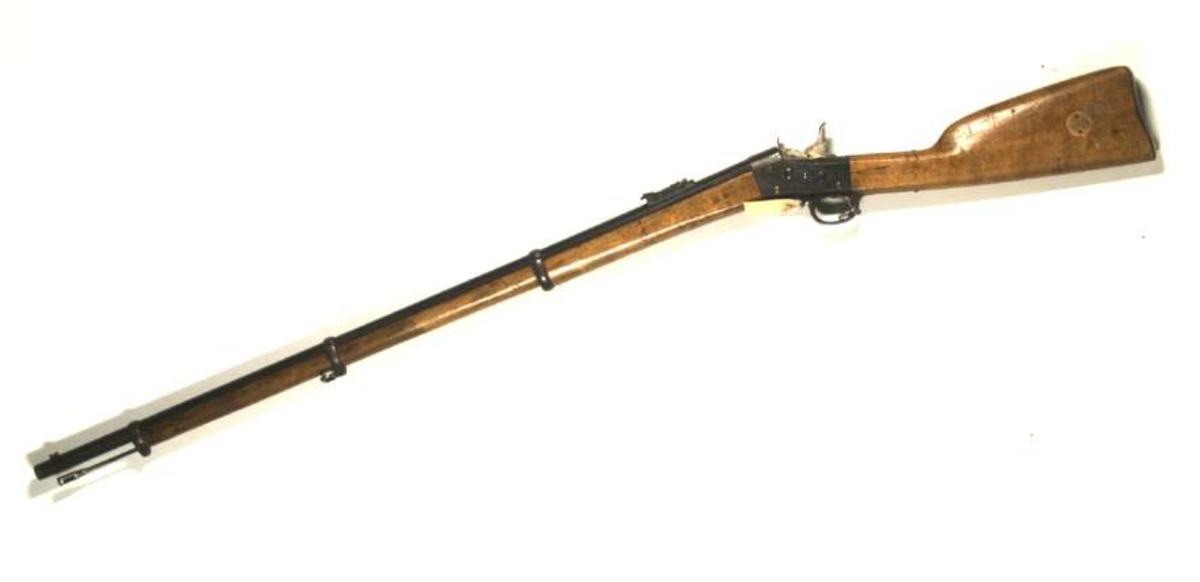 Remington Armé gevär, kaliber 12,7, kantantändning. Märkt '1874' på tre ställen, på ett ställe tillsammans med ett krönt 'C'. Serienummer 14507. På kolven har ett cirkelrunt märke suttit, som dock saknas.