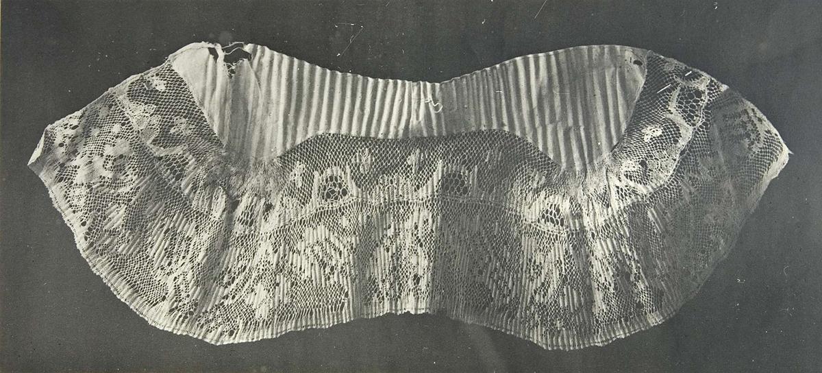 """Fotografi av stycke med knypplade spetsar. I övre högra hörnet är fotografiet märkt """"A.1021."""" I nederkanten står """"LZ"""" och """"9598""""."""