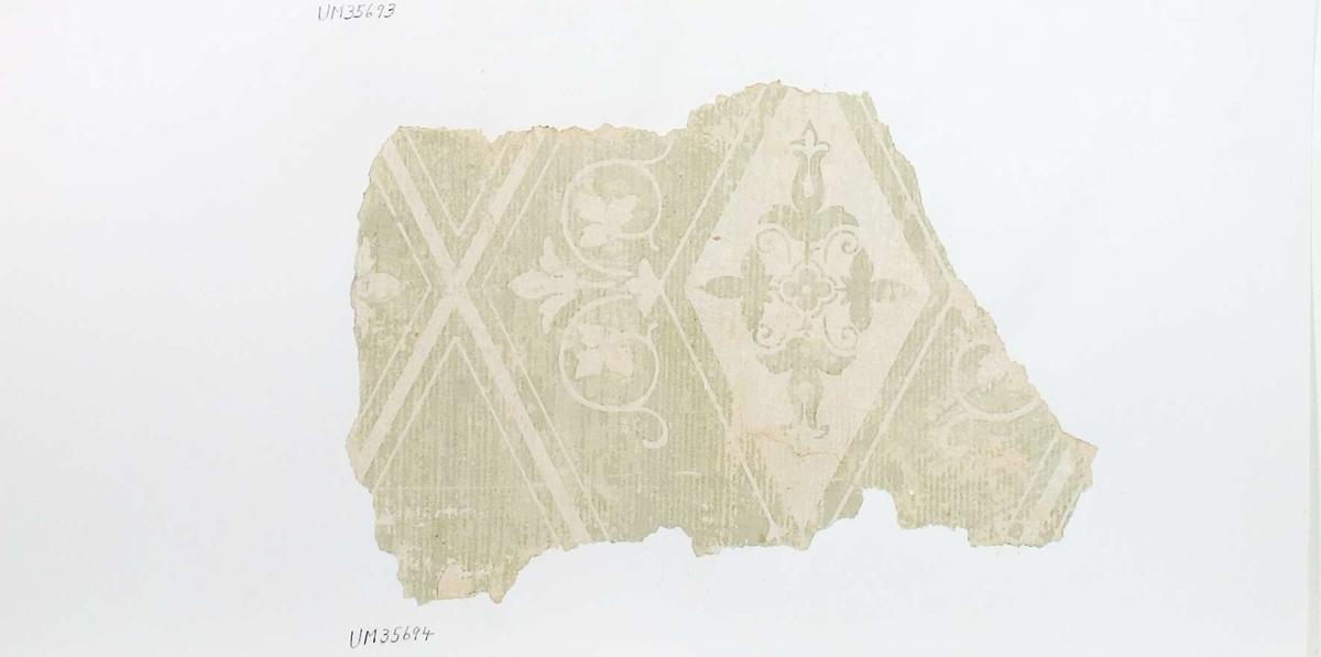 Tapetprov, vitt och ljusgrönt. Text på baksidan av kartongen: 153 Kv. Kaniken Trähuset v. 1 tr Stora mittrummet