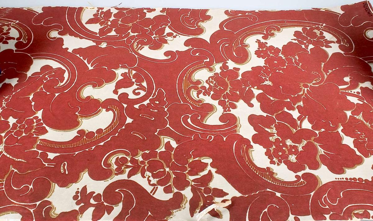 """Ett tapetprov, tryck i rött och guld på vit botten. På baksidan """"förstärkning"""" i form av rutmönster av textil - hampa eller jute."""
