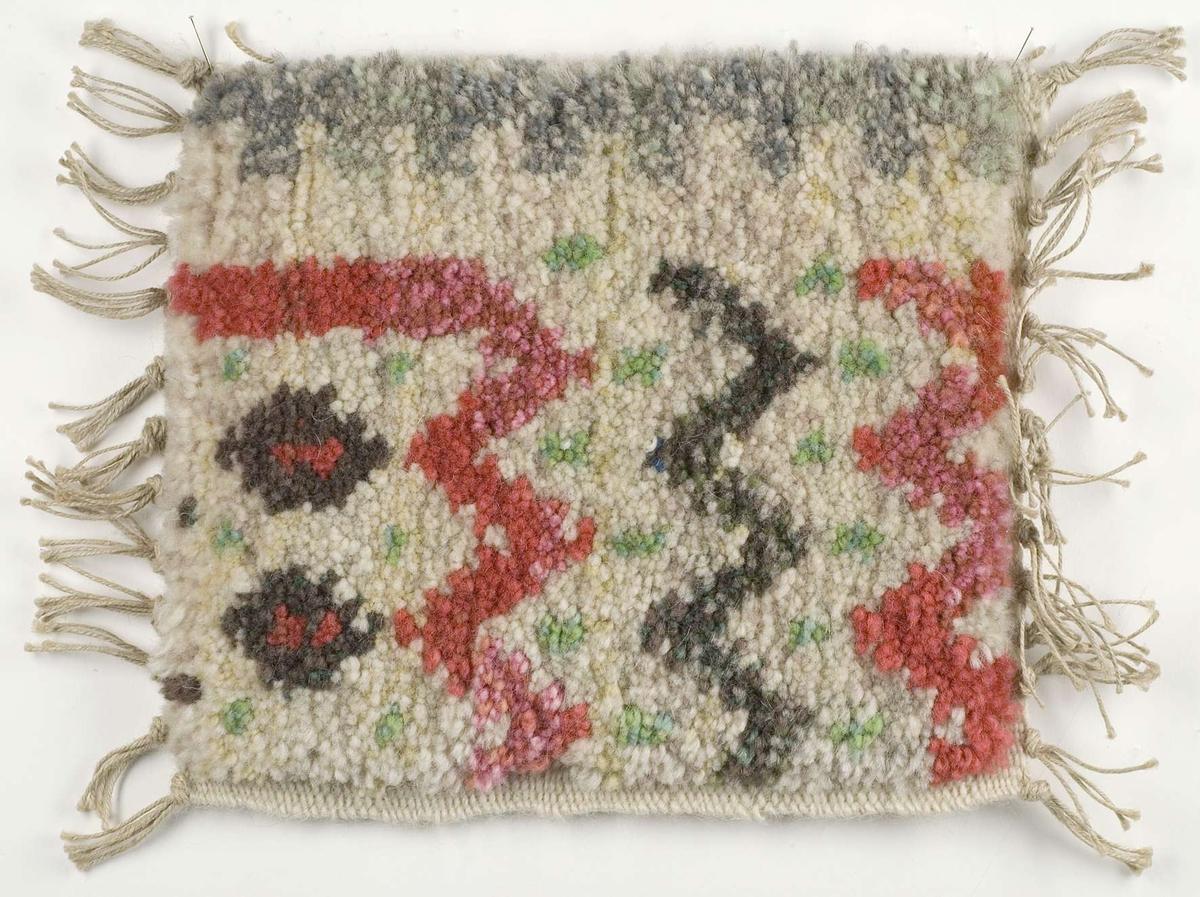 Vävprov av flossamatta. Färgerna på vävprovet är i röda, bruna och gröna nyanser. Enligt tillhörande arbetsritning är det ett prov av en komposition av Ingrid Skerfe-Nilsson. Vävprovet är märkt B2419.
