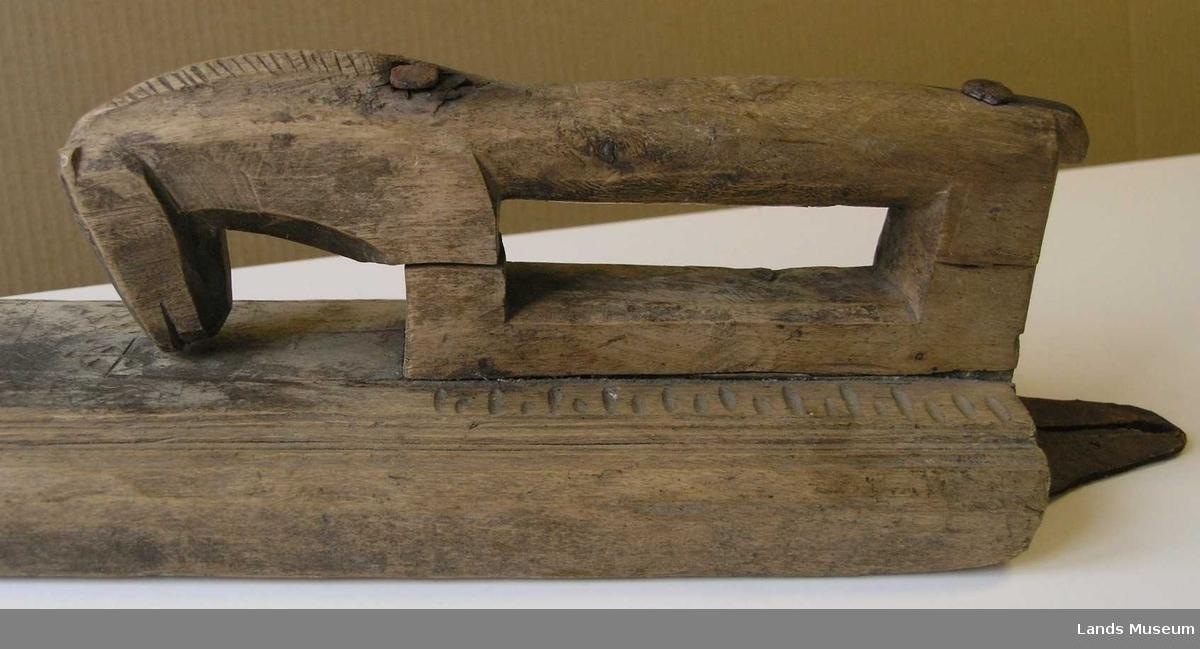 Mangletre med karveskurd og innfelt hesteformet håndtak. Karveskurden viser ulike sirkelmotiv med blant annet seksbladsroser. Mangletreet virker til dels uferdig da noen av motivene i karveskurd virker uferdige, de er påtenget med blyant. Hulkilene i de profilerte kantene er noe ujevne. Håndtakets øvre del har på et eller annet tidpåunkt løsnet og er festet med to metallnagler/spikre. Hesten har tydelig man.