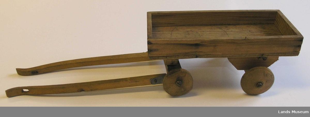 Lekekjerre av tre med skjæker. Hjemmelaget. Har trehjul. Påtegnet sirkler med blyant både under og oppi.