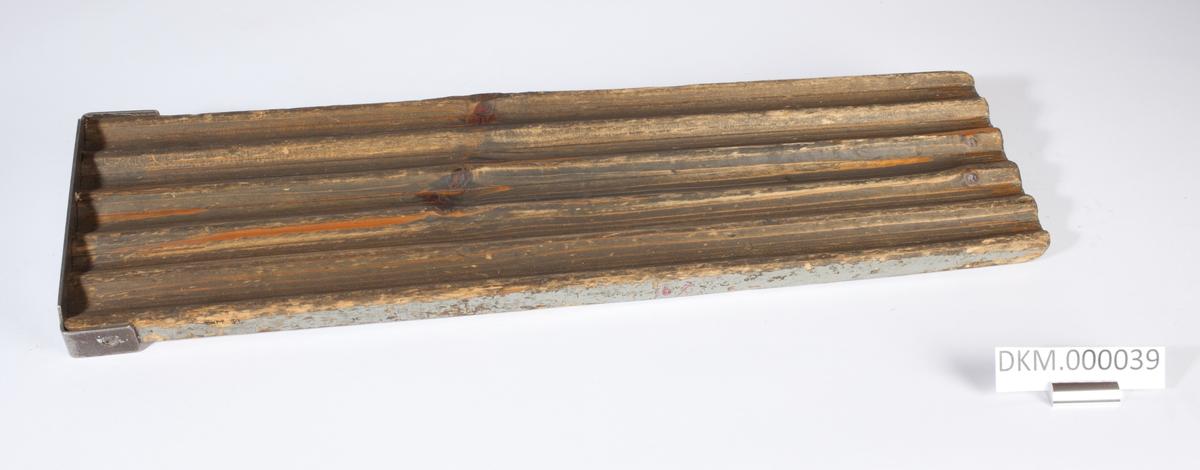 Avlang planke med fem langsgående riller. Rillene er åpne i den ene enden og stengt med jernbeslag i den andre enden.